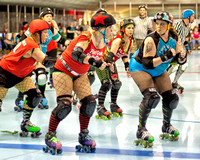 "Colorfully Dressed In Both Expression And Attire, Roller Derby Woman, ""Breasaurus"" Of The Twin City Knockers Prepares To Block in this dramatic event photograph by Brian Buckner Photography."