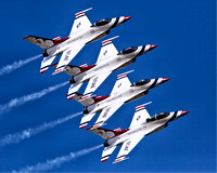 The U.S. Air Force Thunderbirds exhibition flying team cruises by at 700 miles per hour under a blue sky in this commercial aerial photograph by Brian Buckner Photography, Shreveport, Louisiiana.