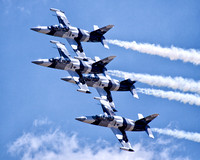 The Black Diamond Jet Team with white smoke billowing from their engines fly in formation at 600 miles per hour above the cheering crowd and under a blue sky with white clouds at an airshow at Barksda