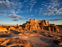 A beautiful sandstone formation in the bisti/de-na-zin wilderness area that looks like a castle made of clay and rock is illuminated by the rays of the dawning sun under a blue sky with striated cloud