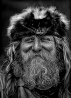 A Smiling Frontier Rendezvous Mountain Man Dressed In Buckskins And Sporting A Hat Made From A Skunk Skin In This In This Black And White Commercial Environmental Portrait By Brian Buckner Photography