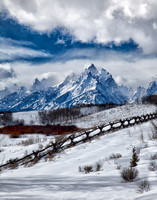 Wispy White Clouds Of Winter, Set Against A Blue Sky, Accent The Snow Covered Peak Of The Grand Teton in this commercial landscape photograph by Brian Buckner Photography, Shreveport, Louisiana.