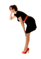 A Woman Is Posing On A Pure White Background With Red Spike High Heel Shoes, A Red Belt, Red Glasses And A Little Black Dress  In This Commercial Advertising Photograph By Brian Buckner Photography.