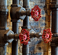Red valve wheels are artisticly shown on an old wall with chipped paint in this commercial architectural photograph by Brian Buckner Photography, Shreveport, Louisiana.