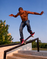 A young, bare-chested or shirtless black man wearing jeans and red tennis shoes performs a skateboard trick by riding on a stair rail using only the front two wheels of his skateboard.