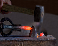 A blacksmith's hammer strikes and cuts through hot glowing iron on the anvil in a forge in this commercial environmental industrial photograph by Brian Buckner Photography, Shreveport, Louisiana.