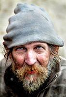 Ricky is a white homeless man wearing a stocking hat and an old green jacket with a heavy grey beard In This Compelling Environmental Portrait or Street Photograph By Brian Buckner Photography.