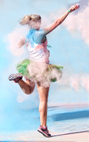 A Female 5K Marathon Runner With A Ballerina's Tutu Costume Celebrates The Finish Of The Race With Some Powder Paint in this artistic event photograph by Brian Buckner Photography, Shreveport.